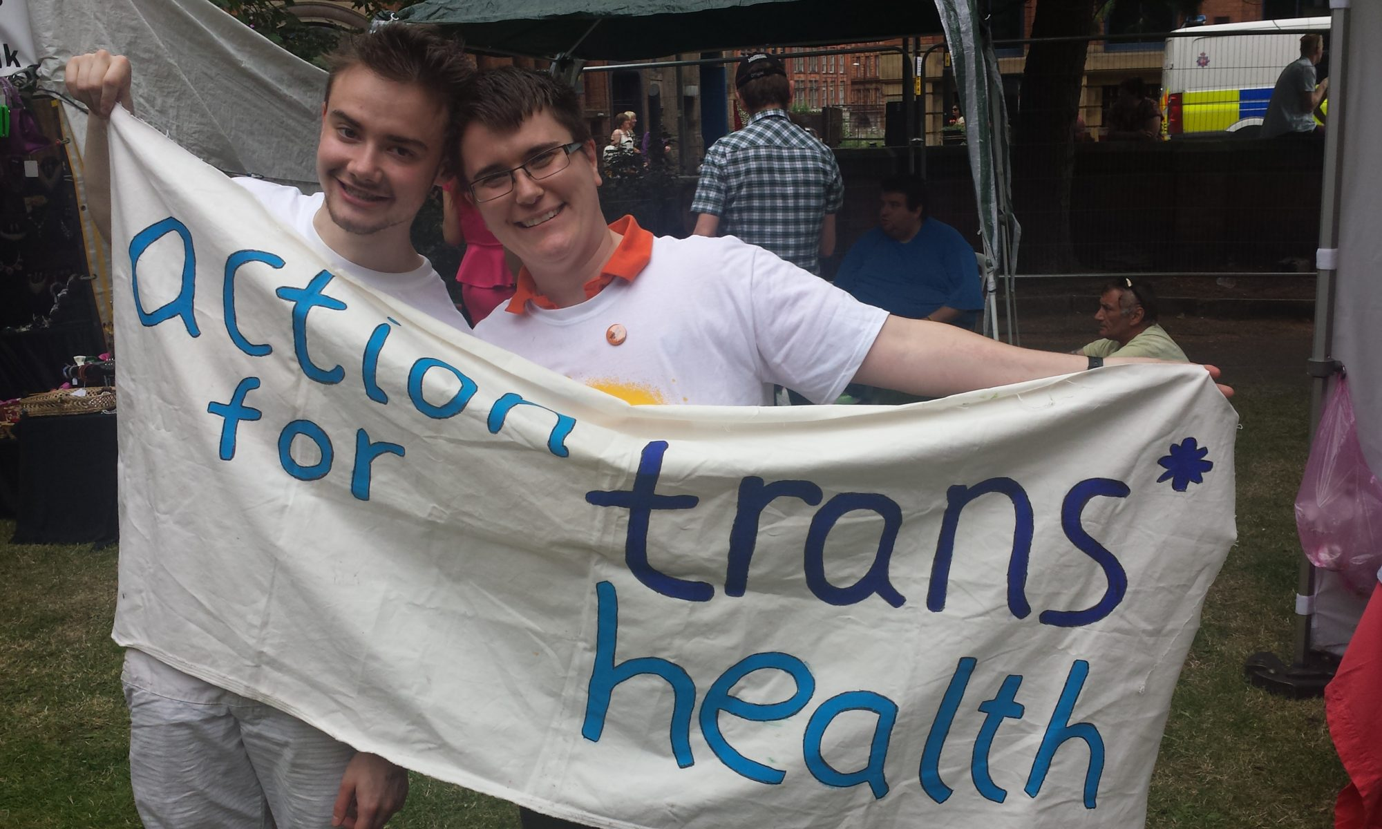 Two men in white t-shirts smiling while they hold an action for trans* health banner for the camera at an event in a park.